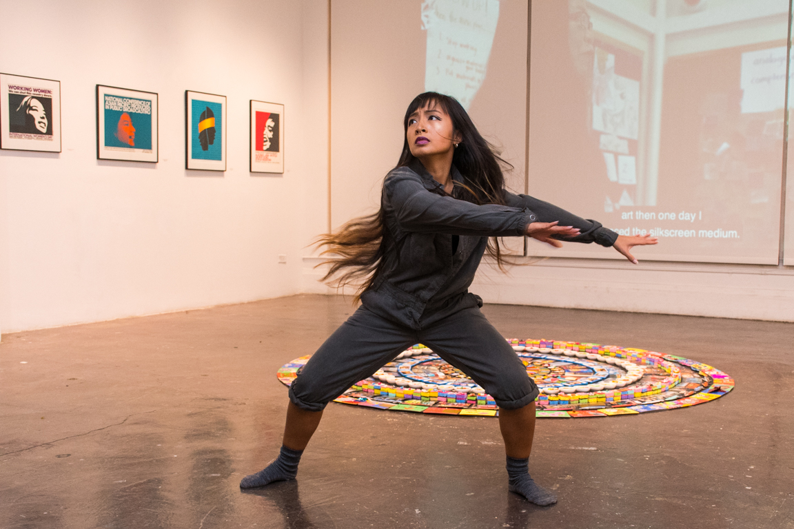 Female dancer stands with her arms outstretched  in front of a mandala.