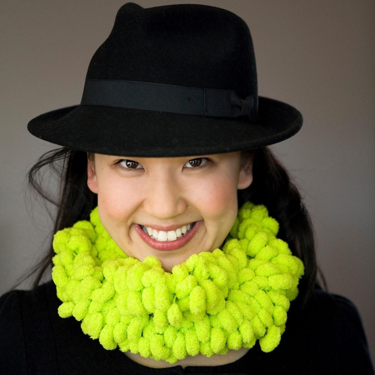 An Asian woman wearing a black fedora hat, facing forward and smiling. She is also wearing a bright lime green textured scarf.