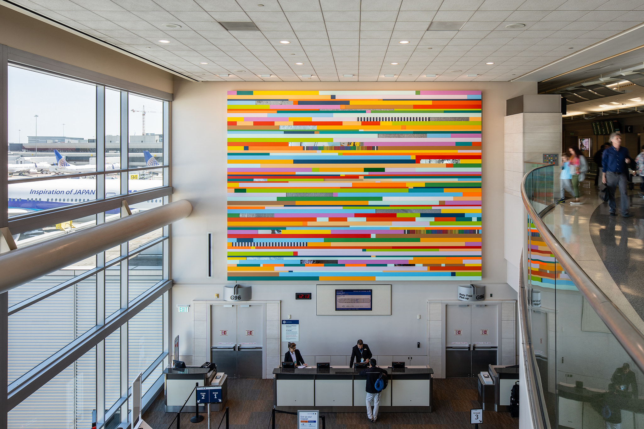 large multi-colored two-dimensional artwork, hanging in airport check-in terminal