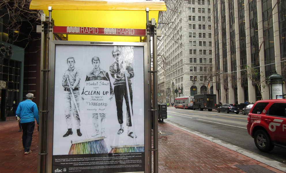 Market street bus kiosk featuring a poster that includes a drawing of three protesters from the 60s
