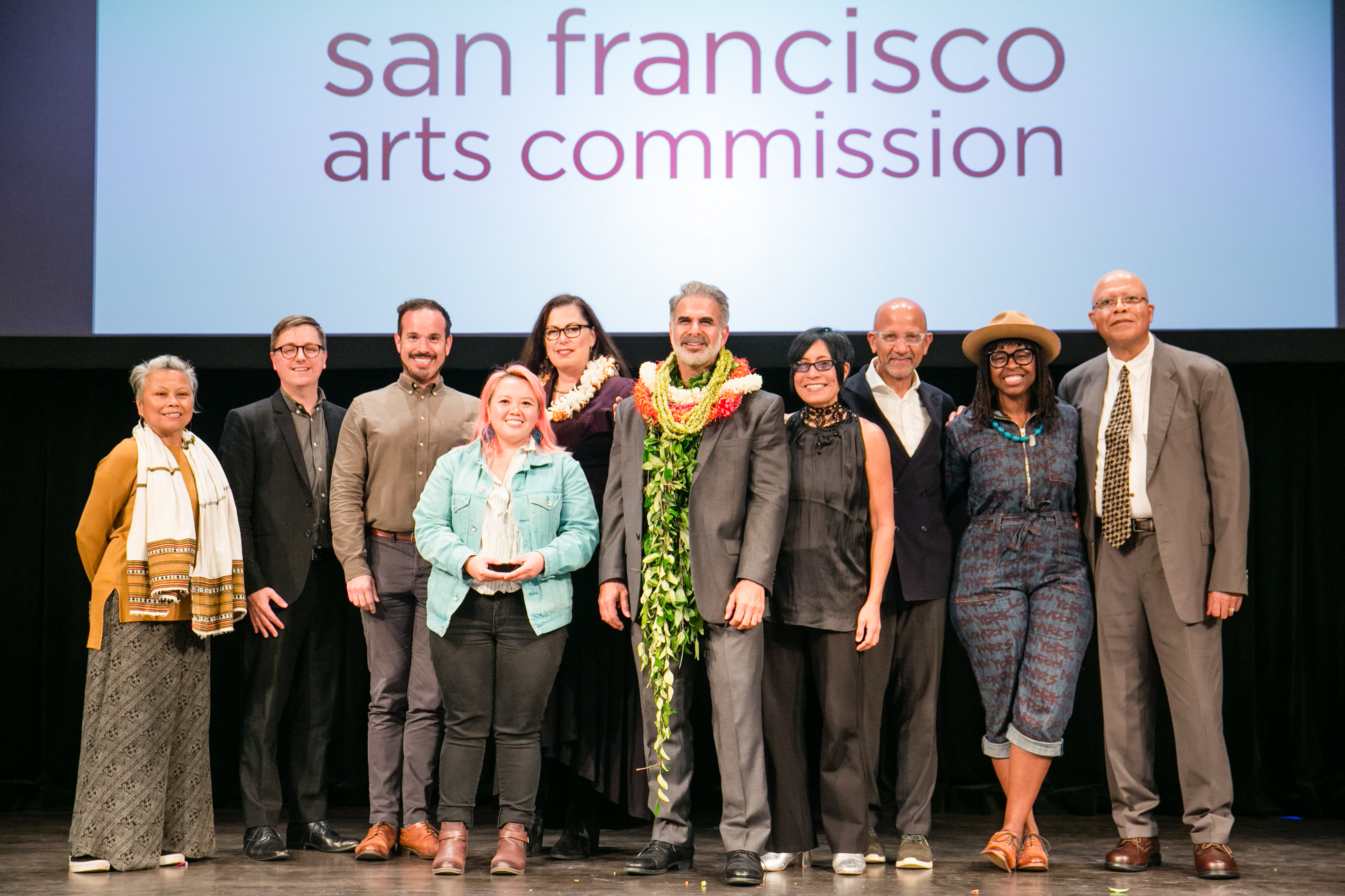 Commissioners, awardees, staff and special guests posing on stage in a group photo at the 4th Annual Grants Convening. Photo: Andria Lo