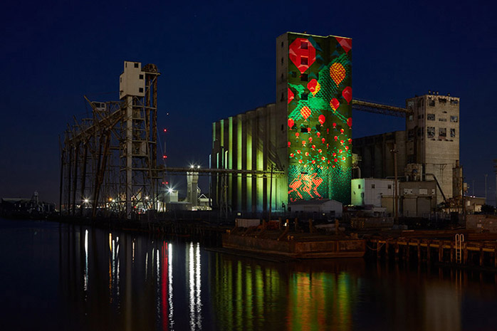 industrial building on the bay with green, red, orange projected onto the side of the building