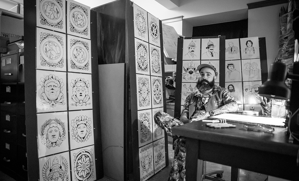 The artist Jeremy Fish sitting at a desk in his City Hall Office surrounded by his drawings