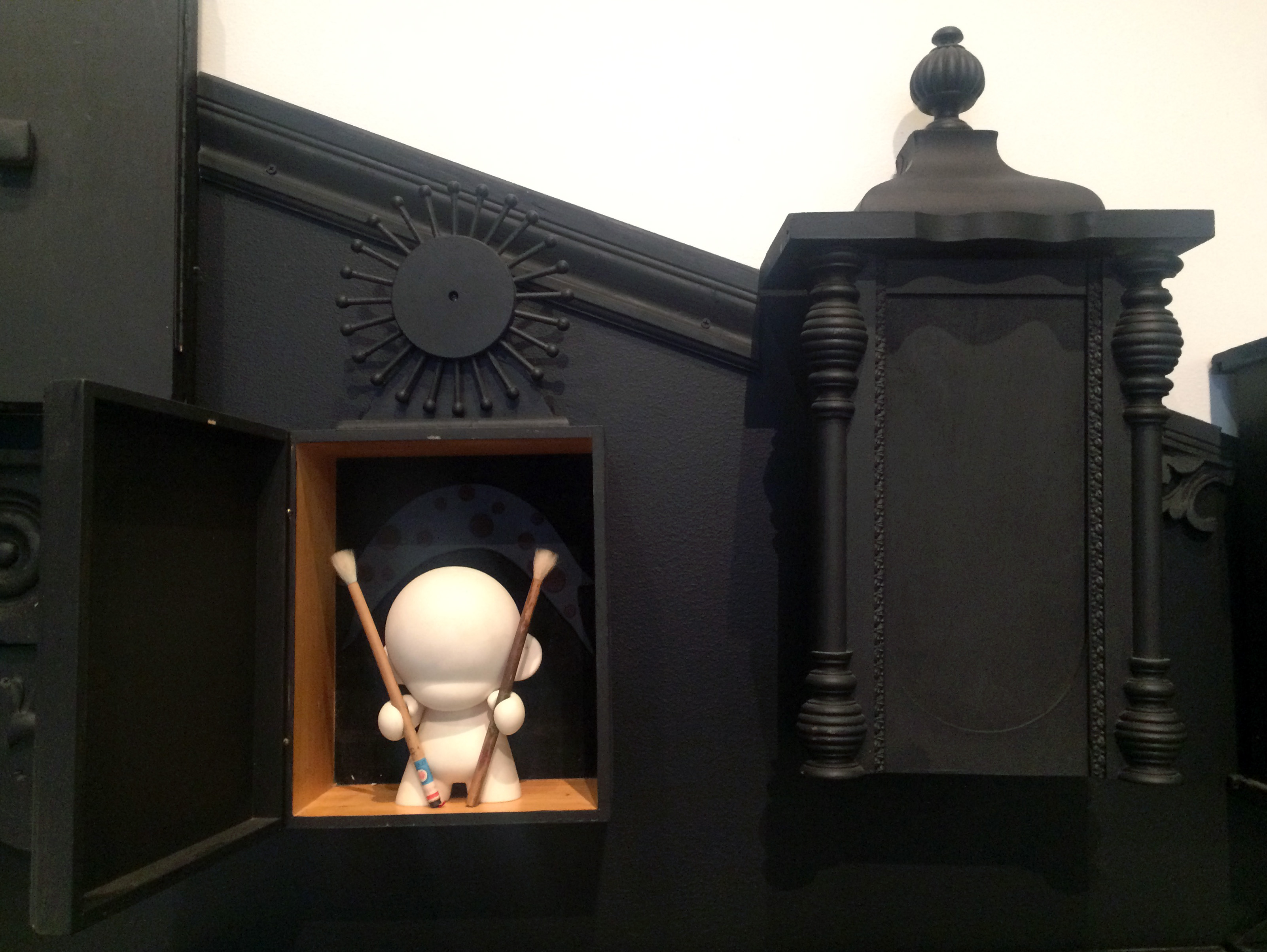A detail of the Wunderkamer showing an open door with a small white sculptural figure.