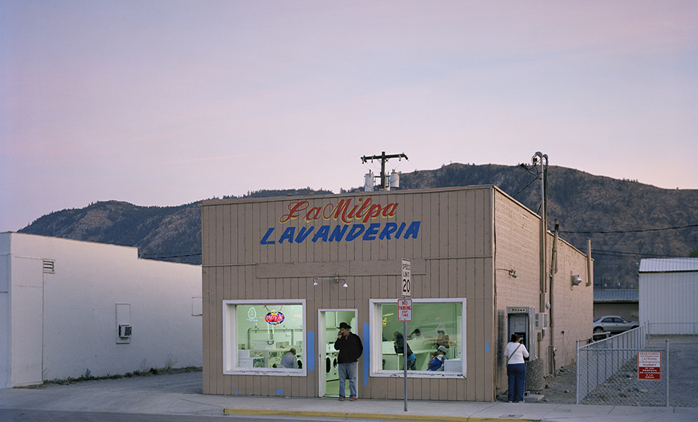 A man standing in front of a laundromat during the dusk.