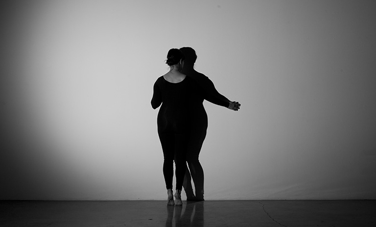 Image of a woman in a black unitard tracing her shadow against a wall.