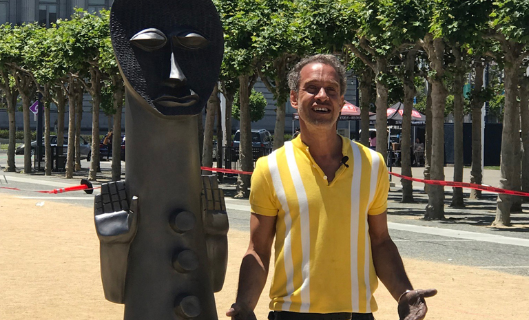 Artist Zak Ove standing next to one of his figures from his installation Invisibel Man and the Masque of Blackness