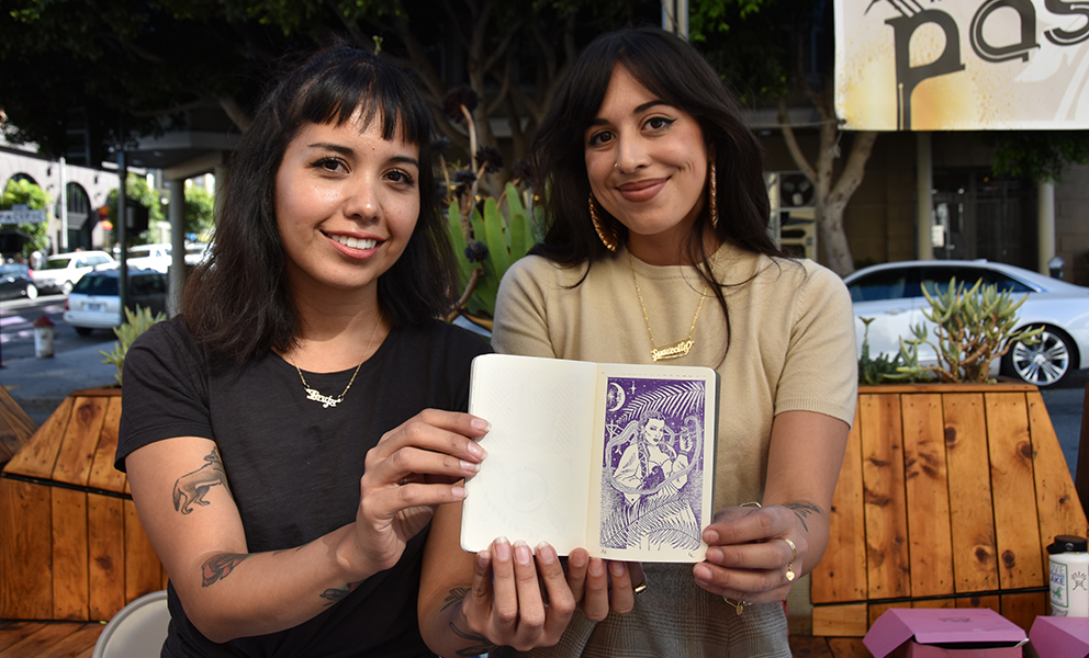Two women hold up a passport with an artist-designed stamp
