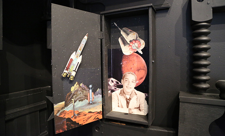 black cabinet with a collage of outer space and a young boy.