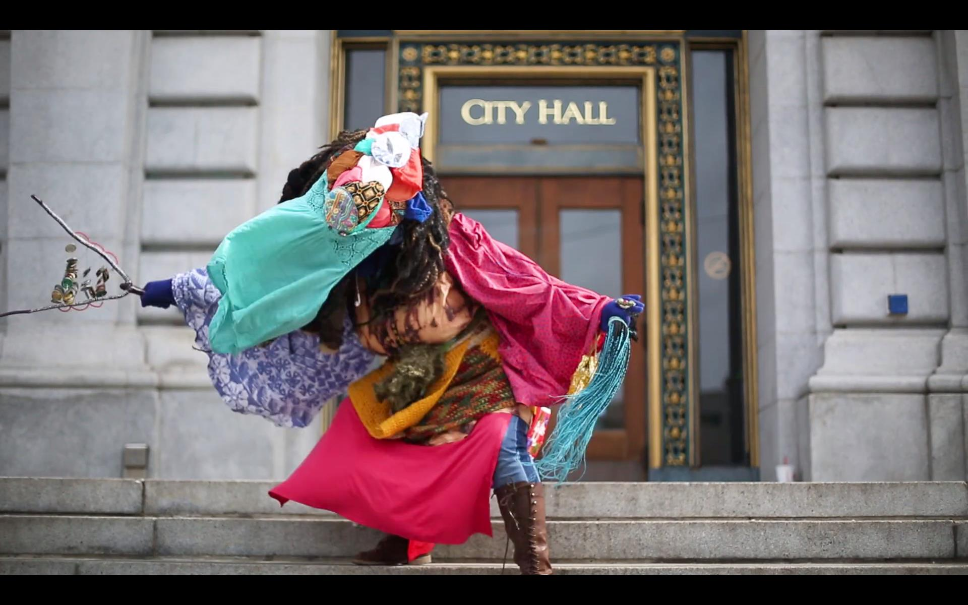 image of costumed healer on the steps of City Hall.