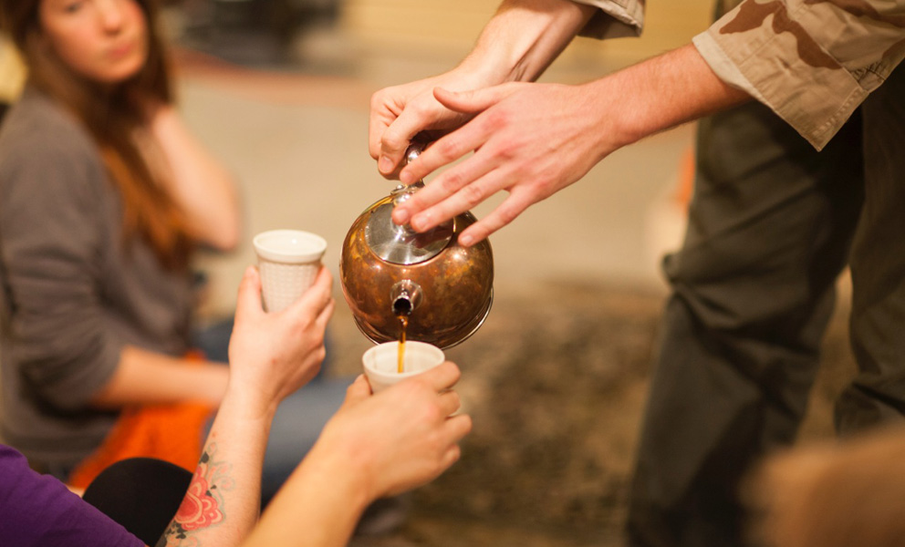 Hands pouring tea into a cup held by an outstretched hand