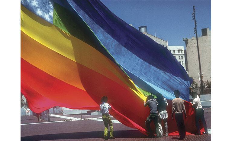 Five people raising a massive rainbow flag.