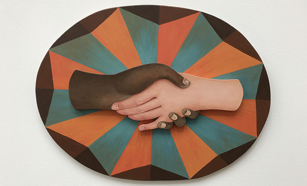 An multi color oval shaped painting of with two different hands clasped in the center