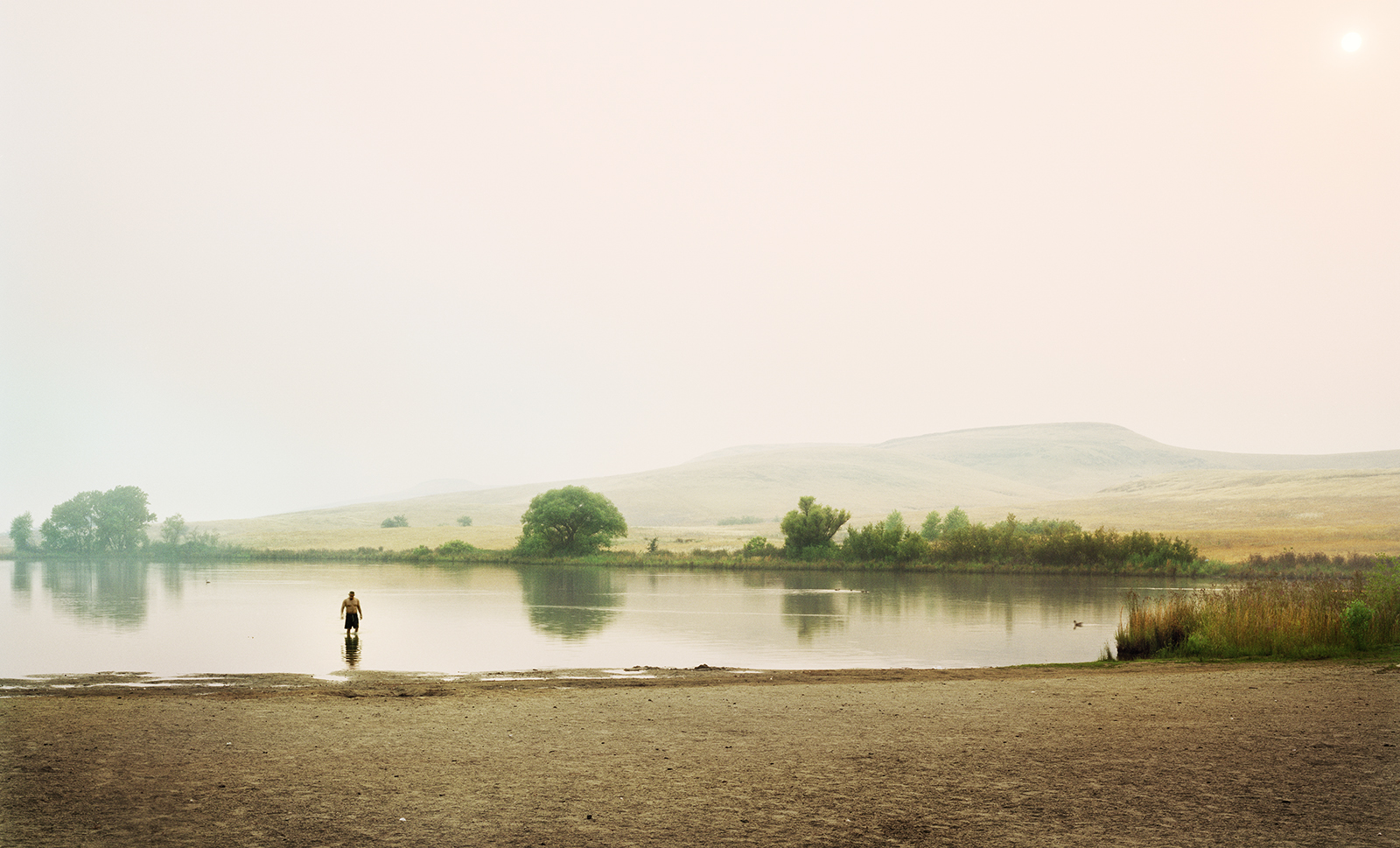 A wide shot of a lake with a man standing in the water