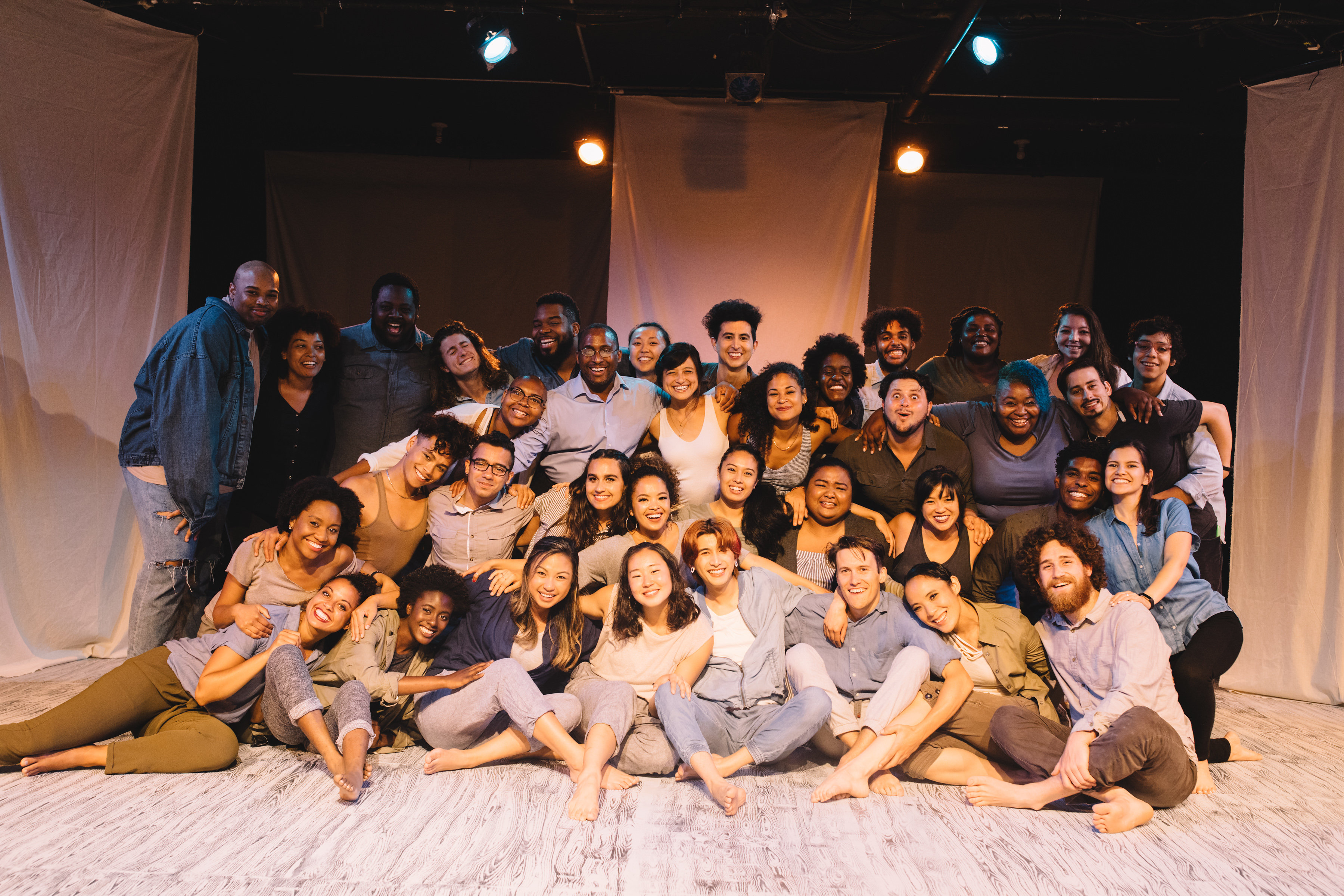A group of a diverse group of theater performers gather on stage.