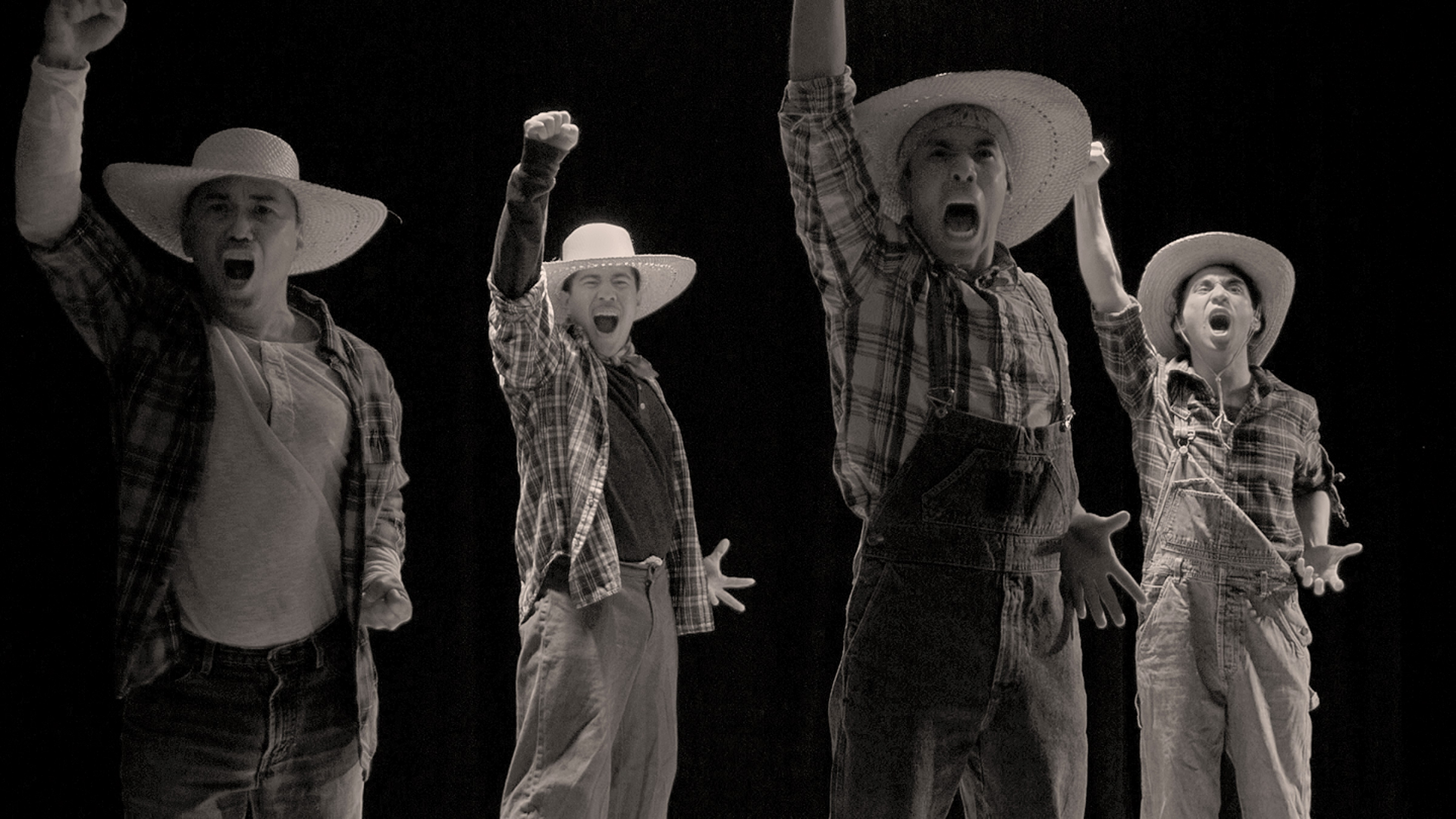 A black and white photo of four men dressed in laborers clothing with their fists raised up in the air and with mouths open shouting.