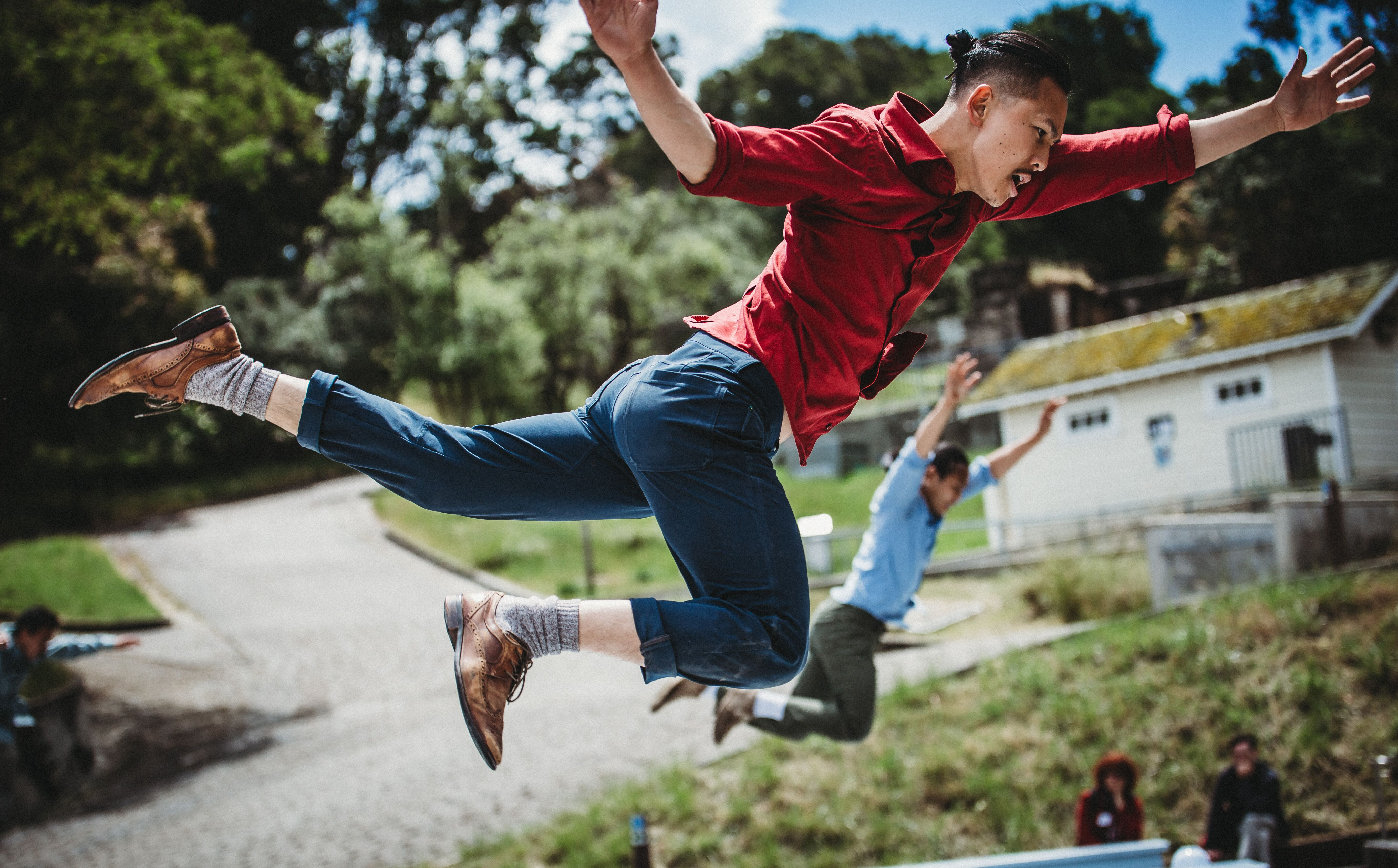 Man in blue jeans and red top flies through the air.