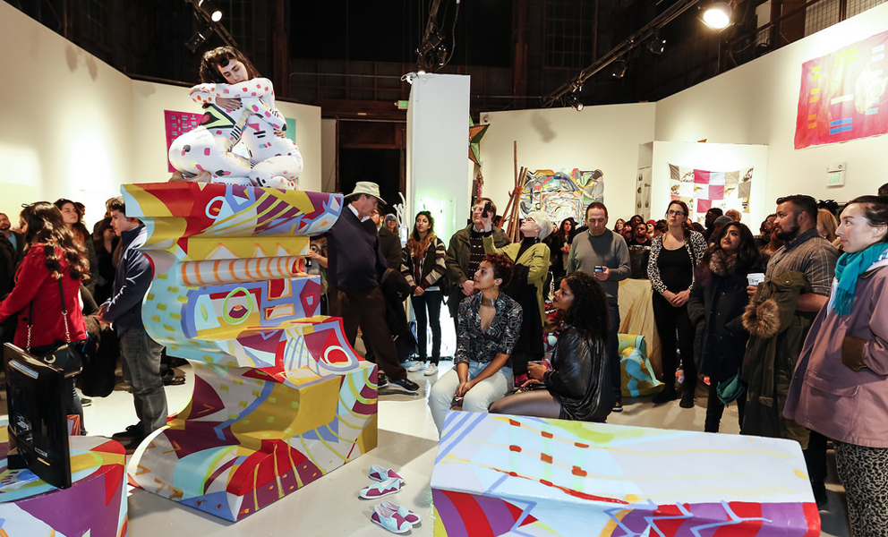 A performance artists crouches on top of a colorful geometric sculpture in the middle of a crows of onlookers