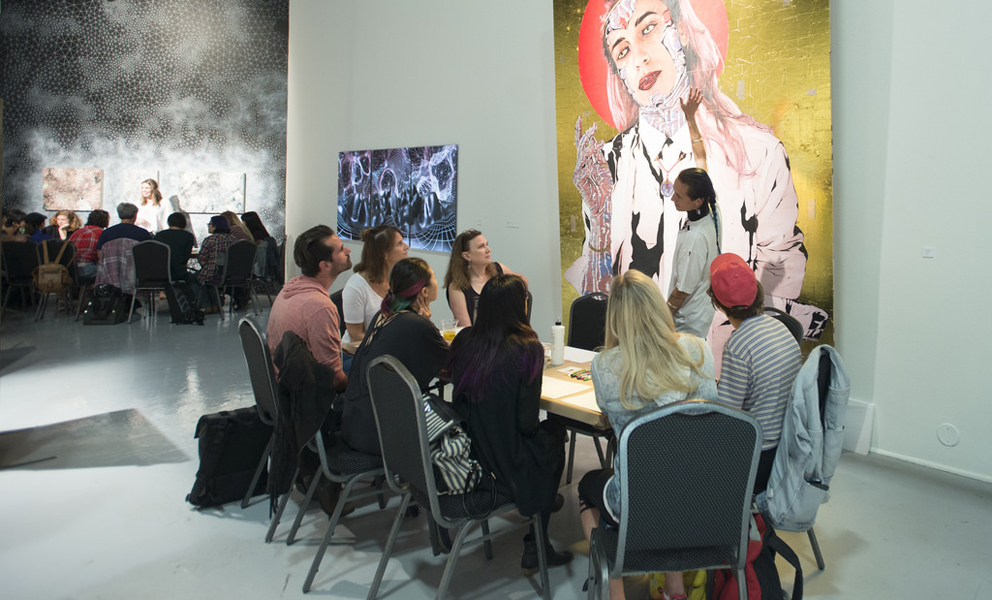 Group of people gathered around a table listening to a speaker in front of a large figurative painting.