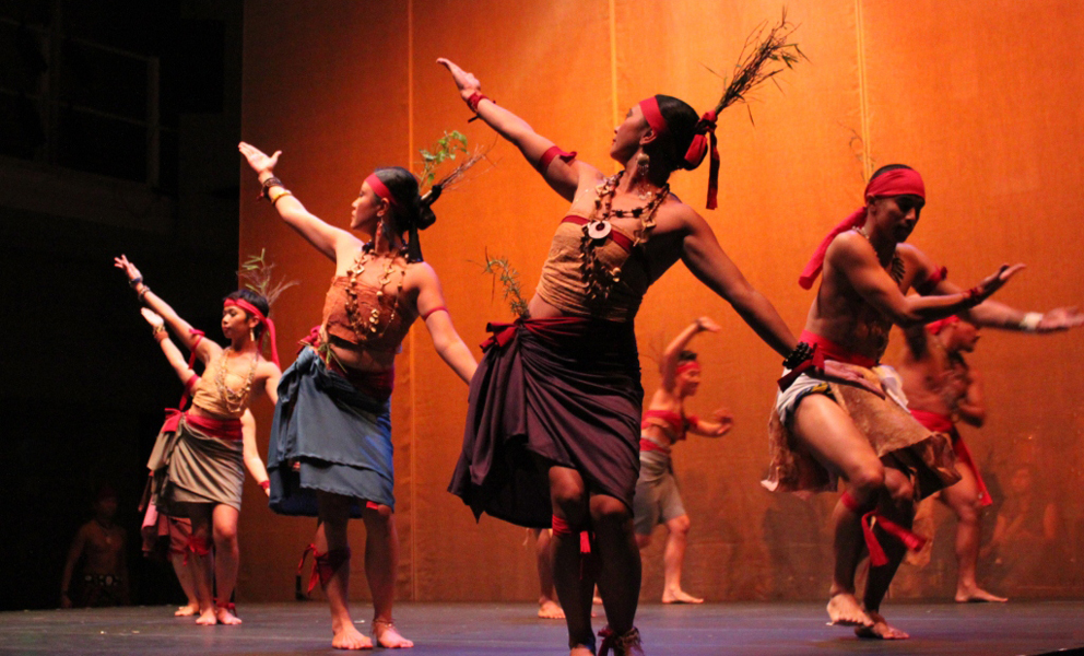 Dancers on a stage with their arms outstreached
