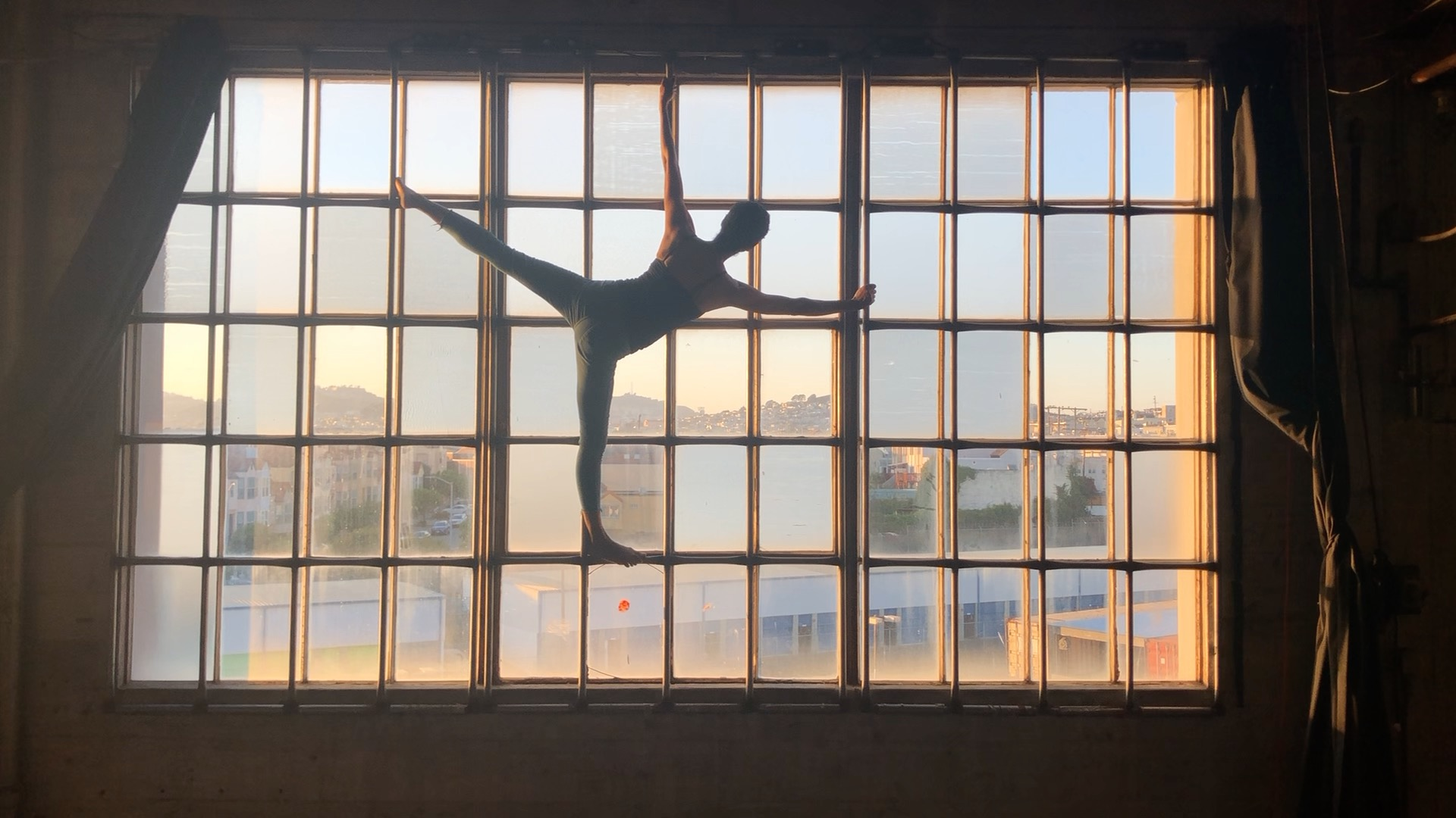 Color photograph of a multi-paned glass window with a person's silhouette in the middle of the frame who is standing on the right leg and outstretched in a posed position.