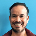 A Latinx man with goatee and smiling, facing forward with a blue background.