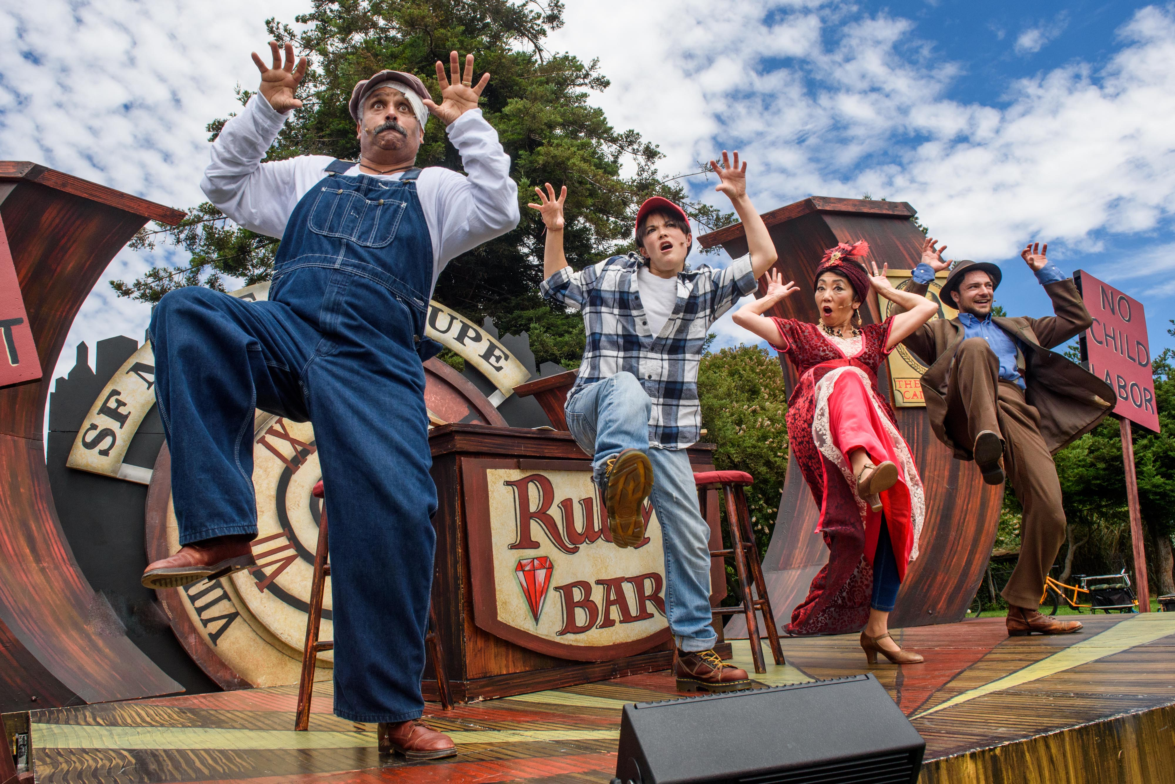 Four mime troupe members dance in unison on an outdoor stage. Bob finds herself on Election Night 1912 in Ruby's Bar with a group of socialists!