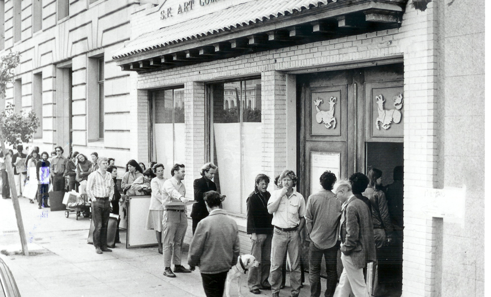 Archival photograph of 155 Grove Street in the 70s. Images shows the storefront with a line of people waiting to get in.