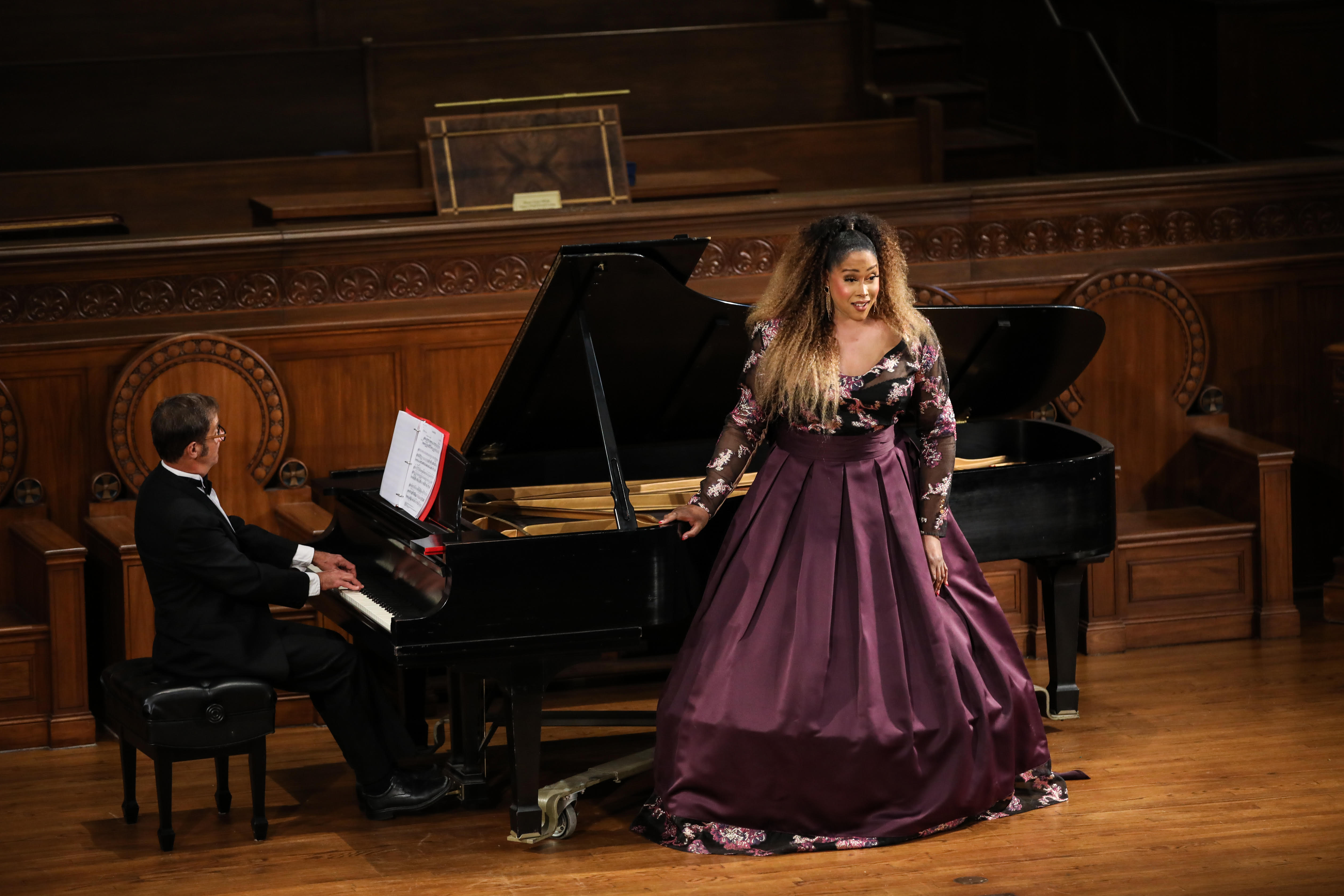 Black woman opera singer with long blond and black hair in a floor length long-sleeved hooped burgundy dress standing in front of a grand piano on stage