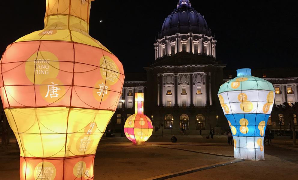 Three colorful large scale lanterns in front of SF City Hall at night.