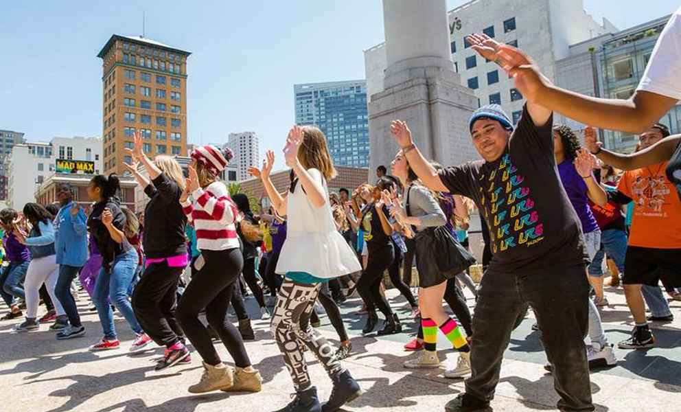 A crowd of people dancing in an oudoor plaza