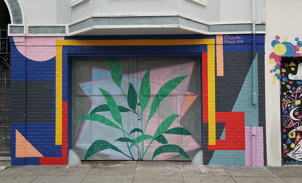 A colorful mural by Michelle Fleck featuring geometric shapes and a plant in green surounded by pastel shapes