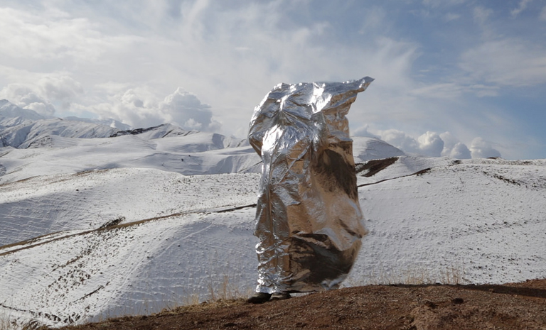 Woman stands in front of a mountain with mylar covering her body