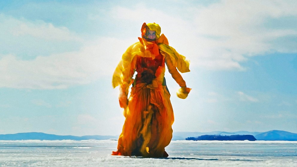 Woman dressed in an orange yellow outfit in an icey landscape