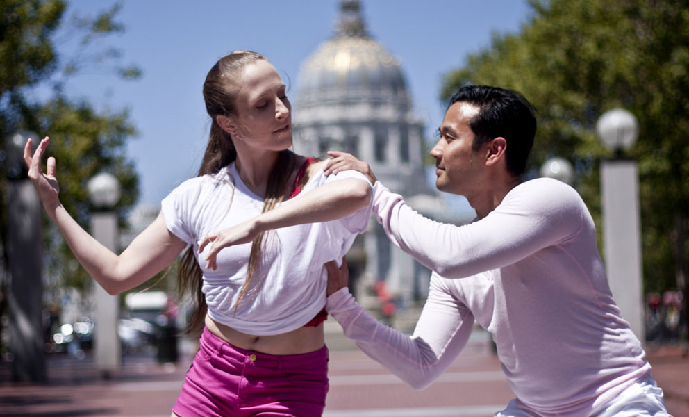 Two dancers dressed in pink and white dancing in front of City Hall
