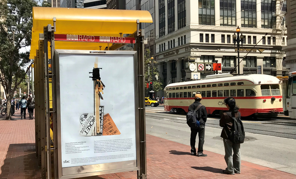 Image of a bus kiosk on Market Street with an image of an amulet by Weston Teruya