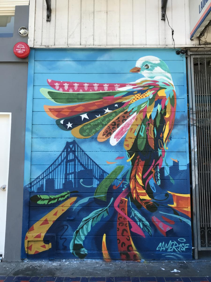Cameron mobergs mural at 2070 mission street pictured right depicts a brightly colored and patterned bird flying above a san francisco cityscape