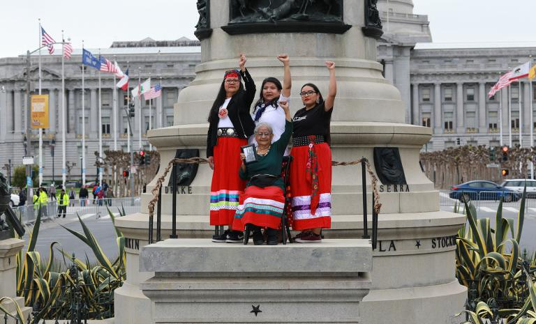 Four Indigenous women standing on an empty pedestal wearing traditional regalia
