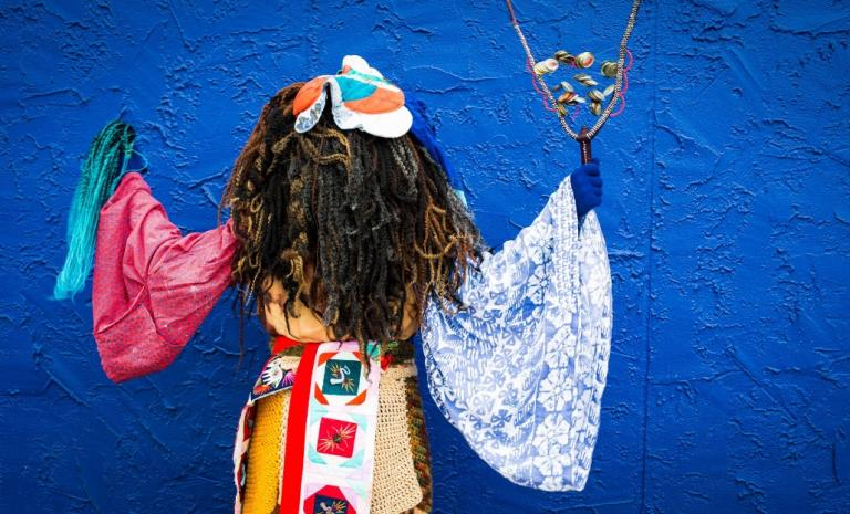 costumed figure against a blue background