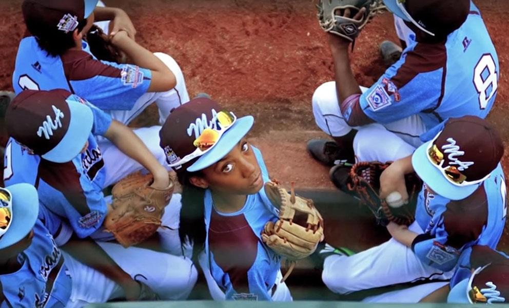image from above of a baseball team in blue uniforms. The central figure, a young woman, is looking up directly into the camera.