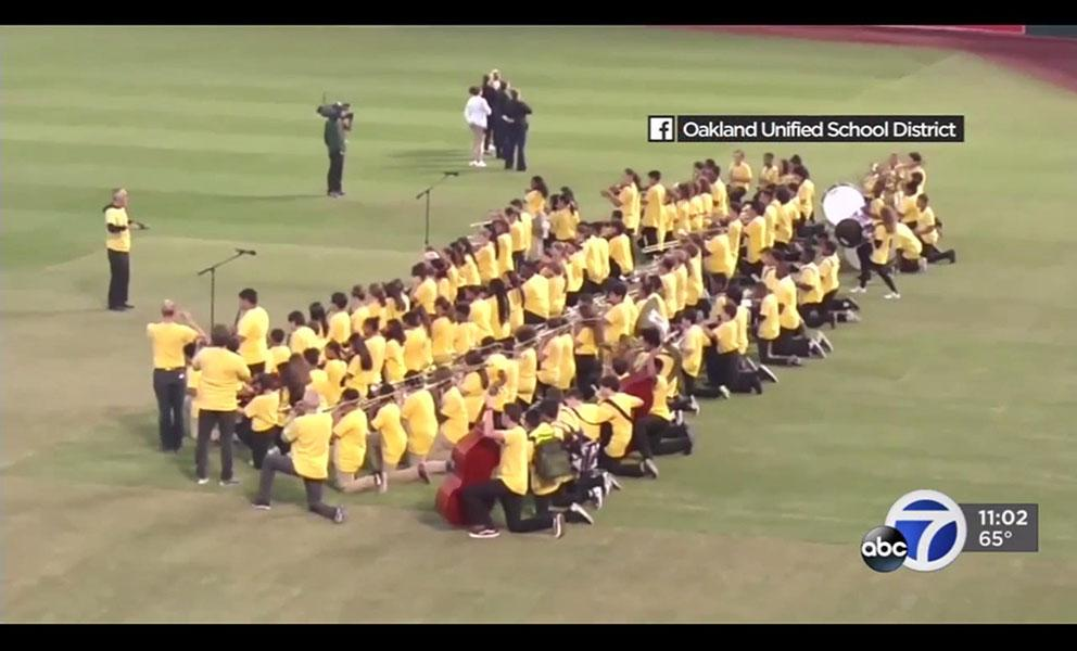 image of a high school marching band taking a knee on a baseball field