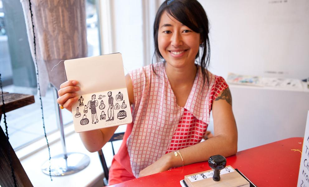 Image of smiling woman wearing red holding a small book with artist designed stamp in it.