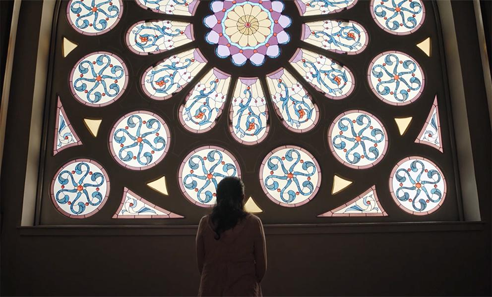 Image of woman standing facing a large stained glass window