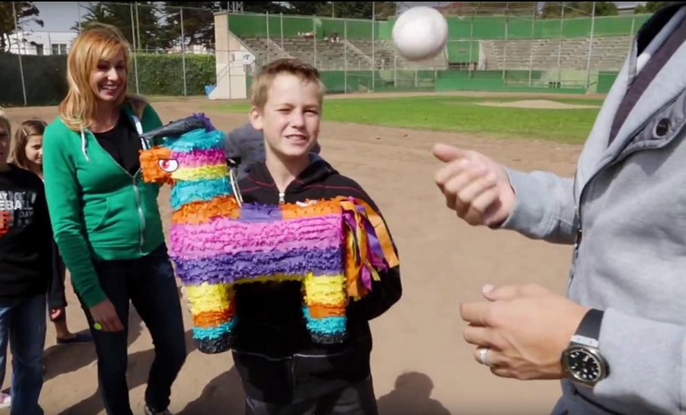 boy holding a pinata outside with man tossing baseball in his hand