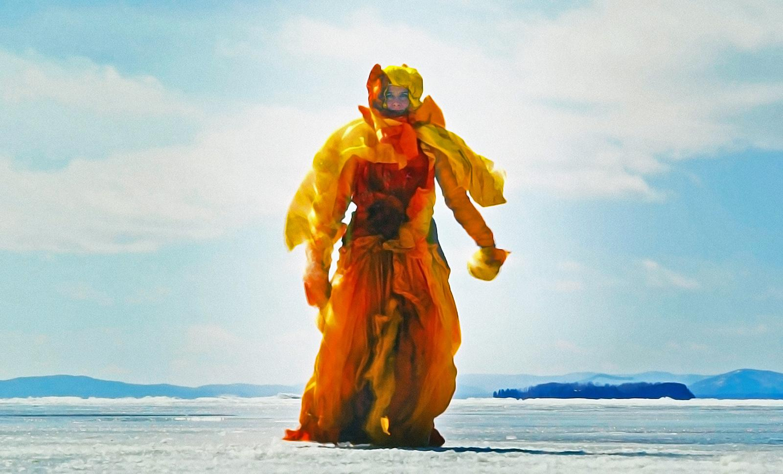 A figure covered except for the face in yellow and orange fabric approaches the camera, walking on a frozen lake