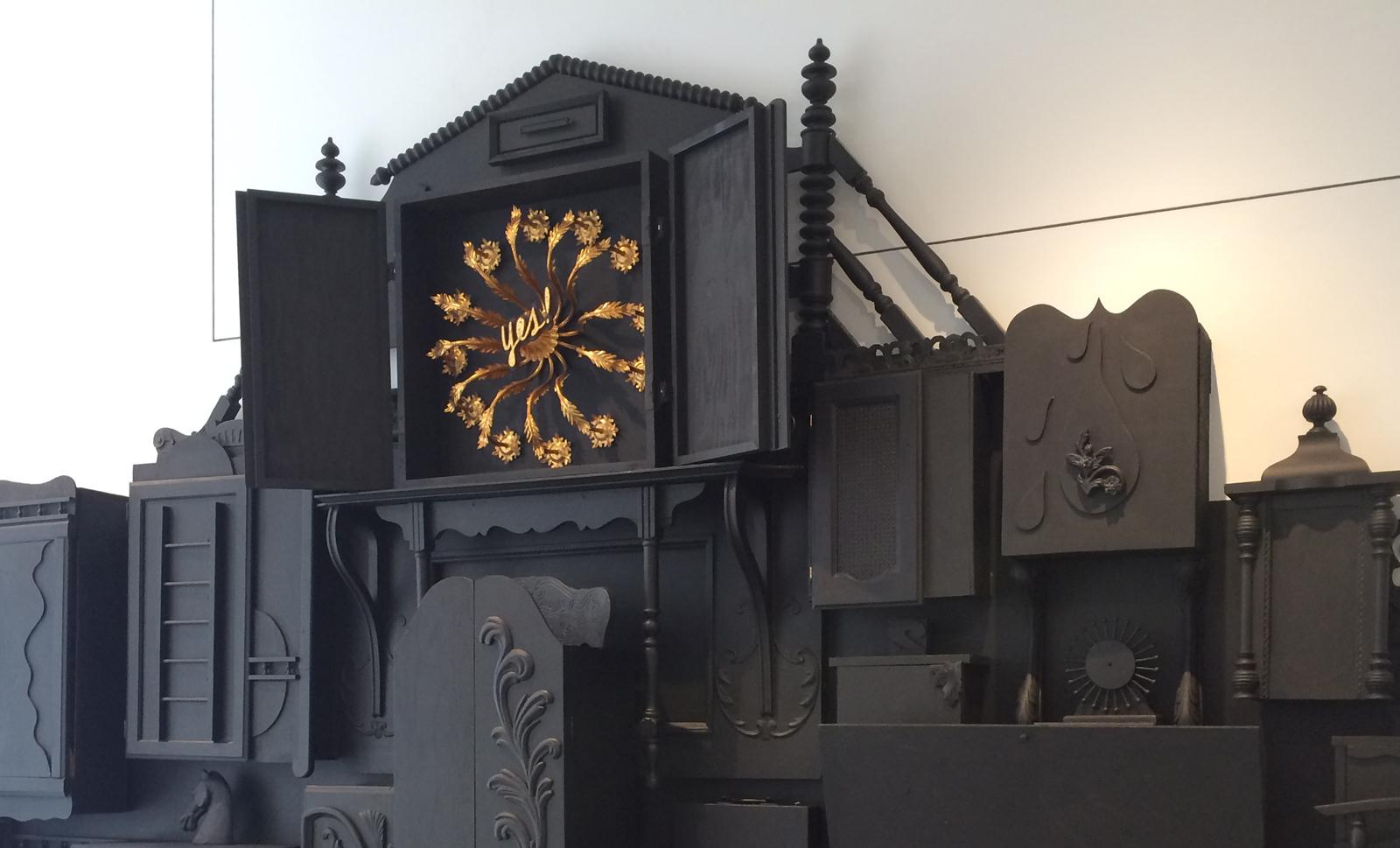 A collection of wood structures painted black. One is open to a collage of found objects.