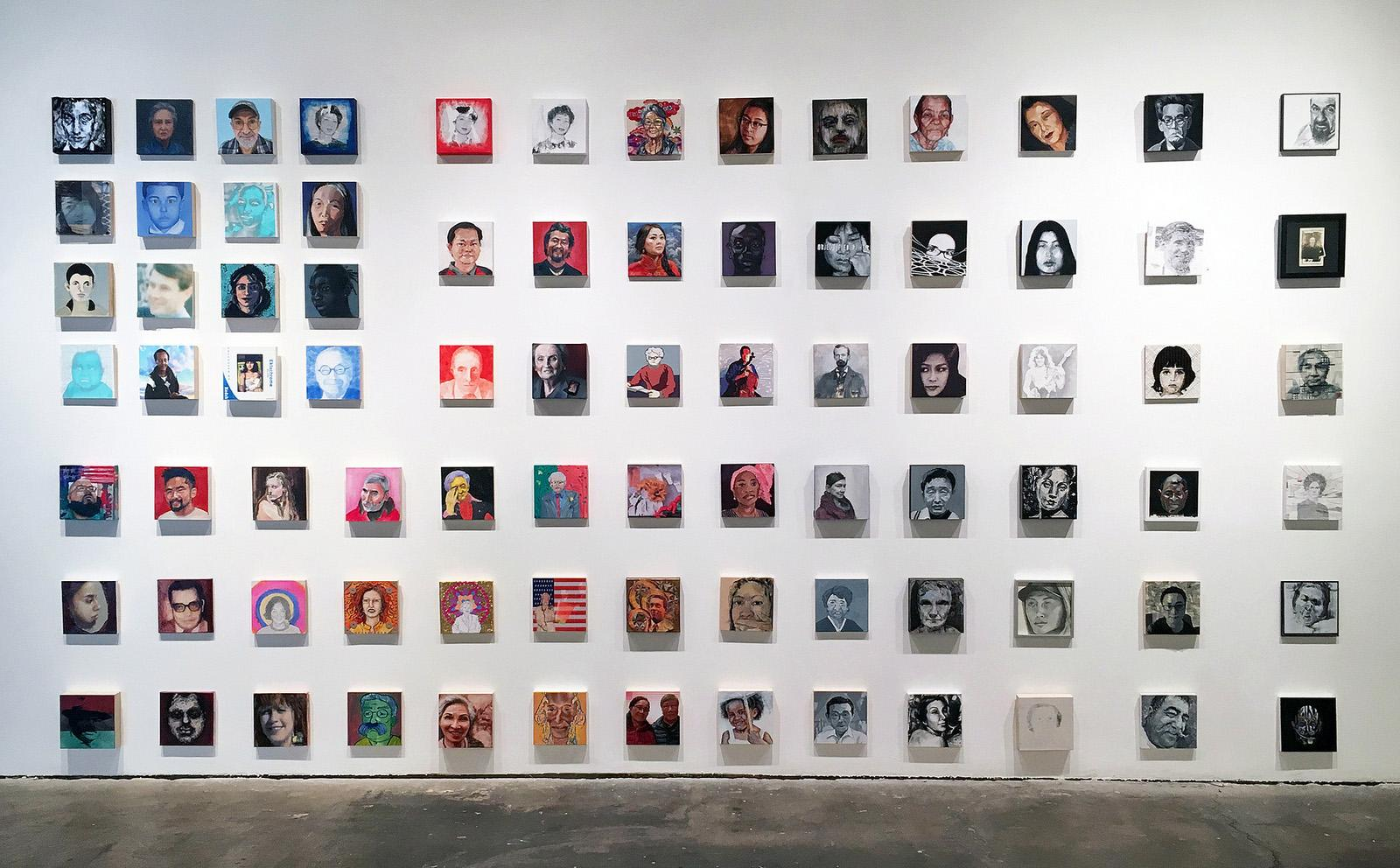 White wall with 125 portraits of immigrants.