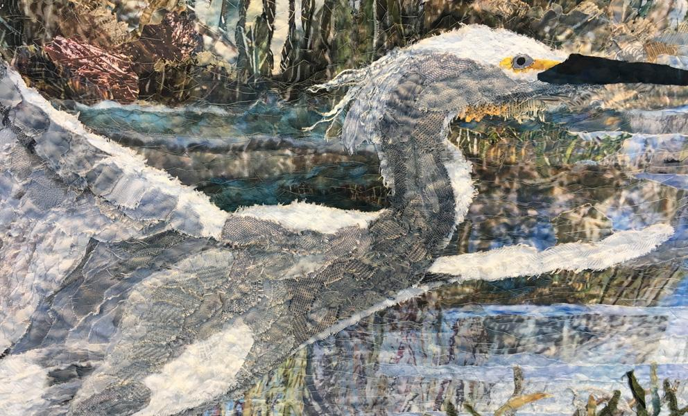 Detail of fabric collage featuring an egret taking flight in a marshland by Merle Axelrod.