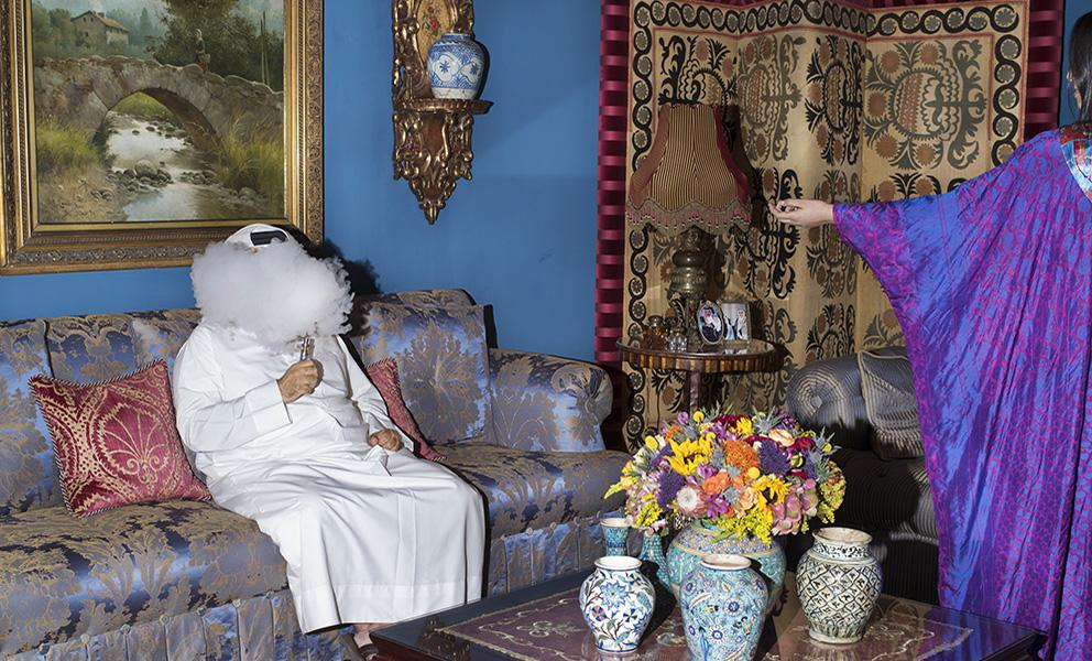 Person sitting on couch in an elaborately decorated living room smoking. Woman in purple gown gesturing toward person on the couch.