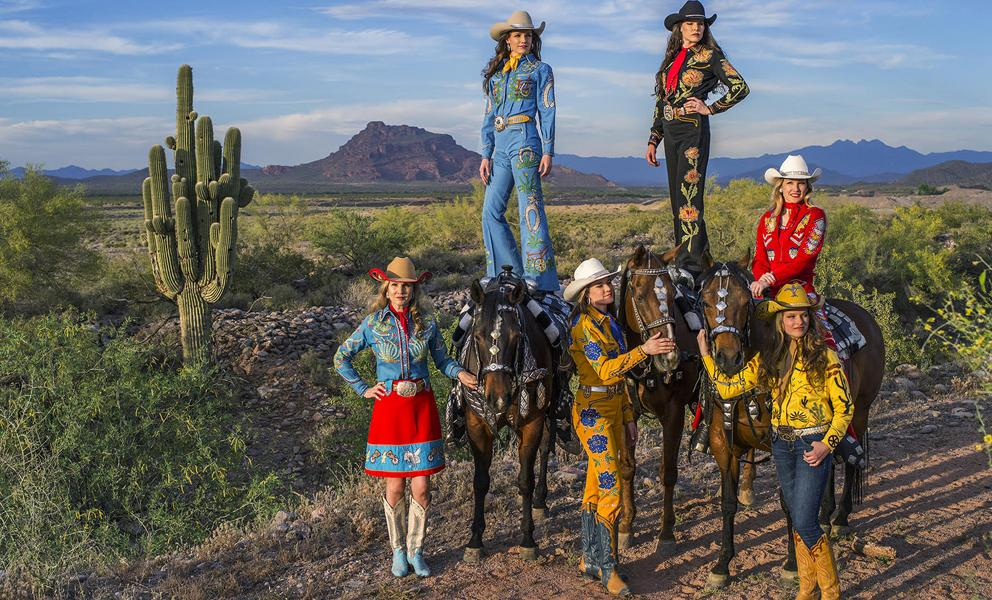 Image of six women dressed in elaborate cowgirl outfits with horses in the dessert
